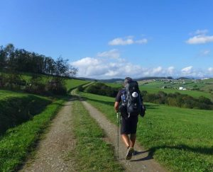 Pilger der durch grüne Landschaft wandert