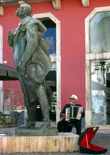 Frühstücksmusik - Der Straßenmusikant beim Sängerdenkmal in Leiria.