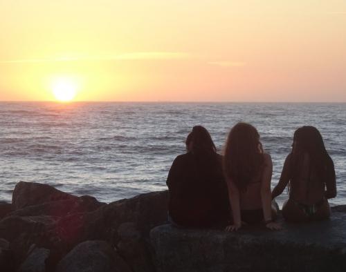 Portugiesische Badenixen genießen den Sonnenuntergang.